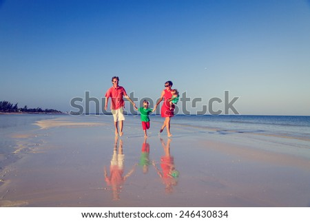 family with two kids having fun on tropical sand beach