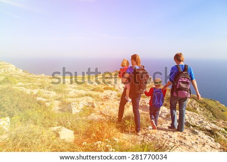 family with two kids hiking in summer mountains