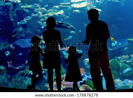 Family with two kids in oceanarium, silhouettes  - stock photo