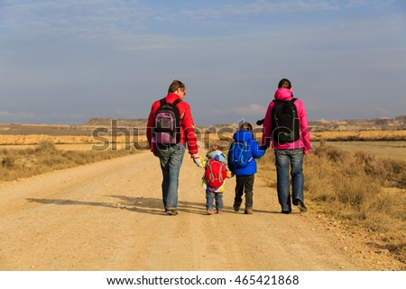 family with two kids walking on scenic road, tourism concept