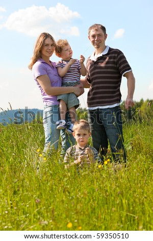 Family with two little boys playing in the grass on a summer meadow carrying one of the kids