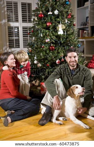 Family with 4 year old boy and dog by Christmas tree - stock photo