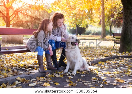 Familywoman And Her Daughter Walk With His Dog Autumn ParkColored Photo