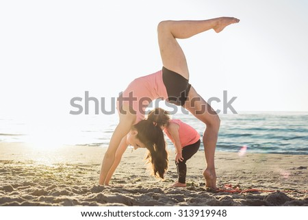 family workout - mother and daughter doing exercises on beach. Mom and child working out on seaside in the morning. Healthy lifestyle concept - stock photo