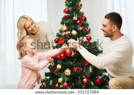 family, x-mas, winter holidays and people concept - happy mother, father and little daughter decorating christmas tree at home - stock photo