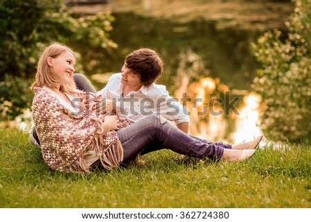 Family (young blond mother, dark-haired father and cute little baby boy) on the bank of a pond on the sunset. Image with selective focus and toning - stock photo