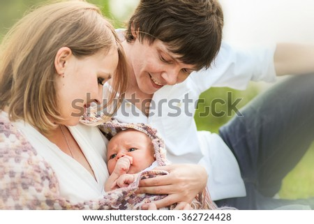 Family (young blond mother, dark-haired father and cute little baby boy) outside sitting on the grass. Image with selective focus and toning