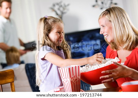 Family: Young Girl Helps Put Popcorn In Boxes - stock photo