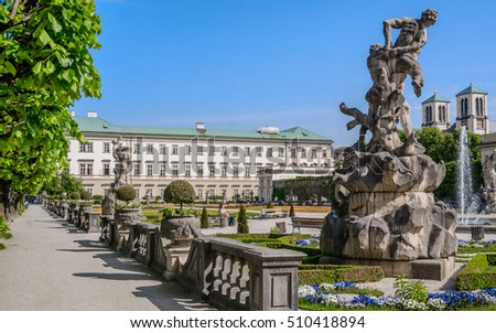 "Famous baroque park ""Mirabell Garden"" (Mirabellgarten - public place). Green flowerbed with walkways in park, any figures and fountains under bright blue sky, Salzburg"