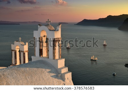 Famous bell towers in the island of Santorini, Greece at sunset