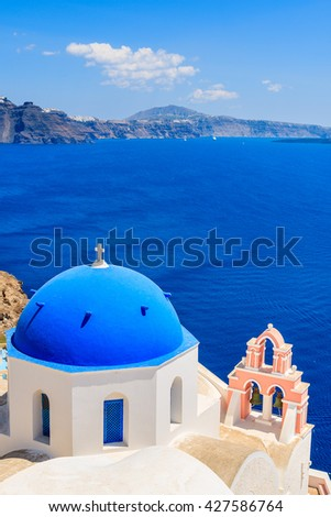 Famous blue dome of a church in Oia village and view of blue sea with caldera on Santorini island, Greece - stock photo