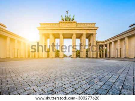 Famous Brandenburger Tor (Brandenburg Gate), one of the best-known landmarks and national symbols of Germany, in beautiful golden morning light at sunrise with lens flare effect, Berlin, Germany - stock photo