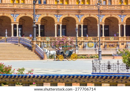 Famous carriages strolling through the Plaza of Spain in Seville, Spain - stock photo