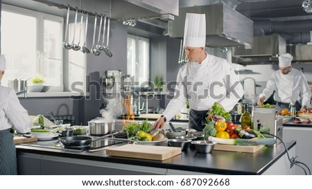 Famous Chef Works in a Big Restaurant Kitchen with His Apprentices. Kitchen is Full of Food, Vegetables and Pans on Fire.