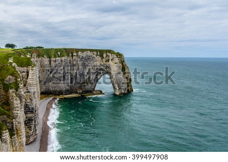 Famous cliffs Aval of Etretat. Etretat is a commune in the Seine-Maritime department in the Haute-Normandie region in northwestern France. Etretat is now a famous French seaside resort. - stock photo