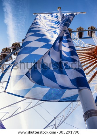 famous ferris wheel at the oktoberfest in munich and bavarian flag - germany - stock photo