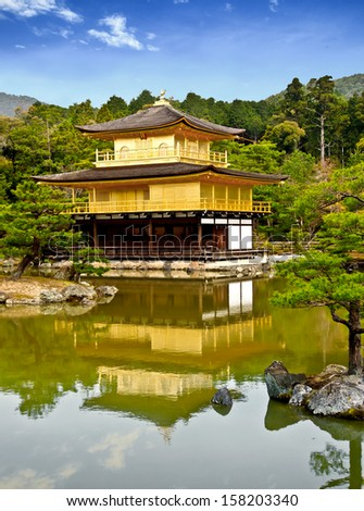 famous golden pavilion at Kinkakuji temple with blue sky, Kyoto, Japan (composition) - stock photo