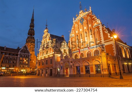 Famous House of Blackheads on the Town Square in Riga with a Church of St. Peter in the back. Latvia, after sunset.  House of Blackheads, destroyed during 2 World War, was reconstructed in the 1999. - stock photo