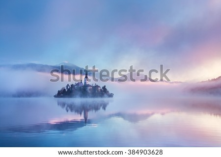 Famous island with old church in the city of Bled. Misty morning with gorgeous lights and colors. Alps mountains in the background. Slovenia, Europe - stock photo