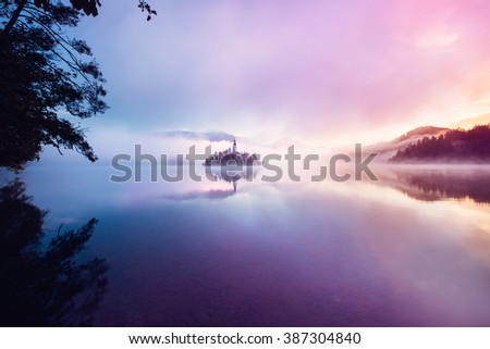Famous island with old church in the city of Bled. Misty morning with gorgeous lights and colors. Alps mountains in the background. Slovenia, Europe (Blejsko jezero) - stock photo