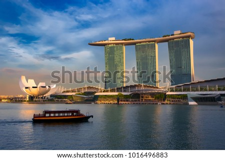 Famous landmark Marina Bay Sands hotel reflected in water at golden sunset. Singapore city landscape