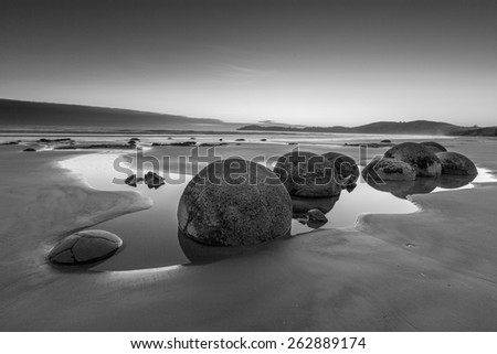 Famous Moeraki Boulders at sunrise, Koekohe beach in black and white ,Otago, South Island, New Zealand - stock photo