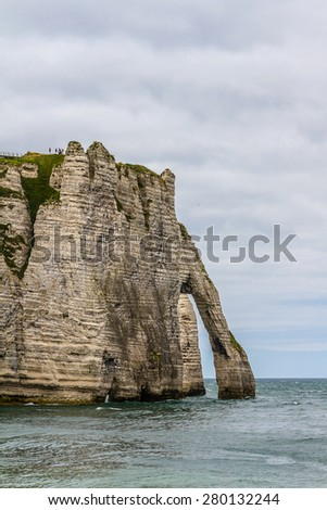 Famous natural cliffs in Etretat. Etretat is a commune in Seine-Maritime department in Haute-Normandie region in France. Etretat is now a famous French seaside resort. - stock photo