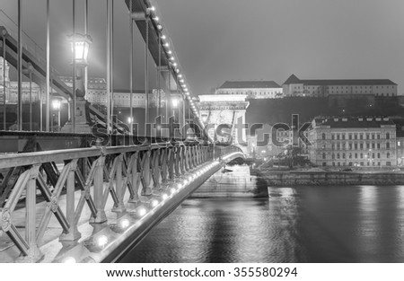Famous old chain bridge in Budapest at night in black and white - stock photo
