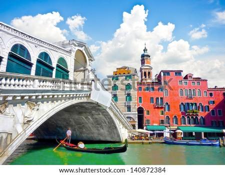 Famous Ponte di Rialto with traditional Gondola under the bridge in Venice, Italy - stock photo