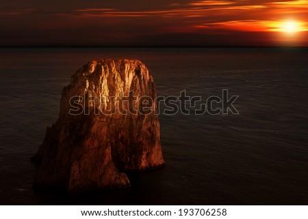 Famous rocks (Faraglioni) on the island of Capri, sunset  - stock photo