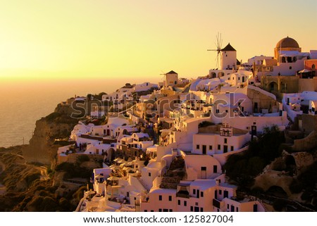 Famous sunset view of Santorini, Greece with traditional windmills and white houses - stock photo