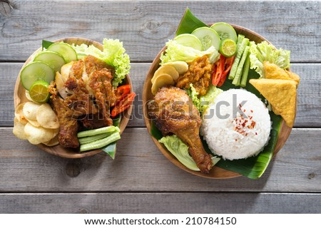 Famous traditional Indonesian food. Delicious nasi ayam penyet with sambal belacan. Fried chicken rice. - stock photo