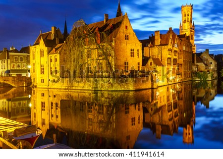 Famous view of Bruges, Belgium - Rozenhoedkaai with Belfry and old houses with reflection along canal with tree at night.