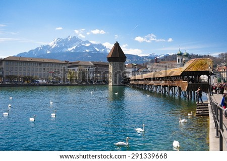 Famous Wooden Chapel Bridge, White Swans on Lucerne Lake and  Snow-capped Mountain in Luzern, Switzerland