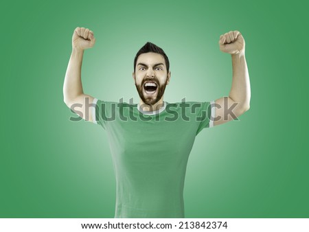 Fan in green and white t-shirt celebrates on green background - stock photo