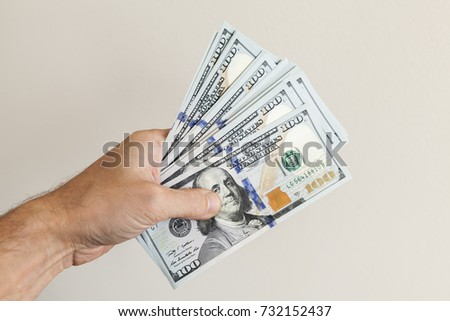 Fan of 100 Dollars notes in male hand over gray wall background