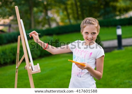 Fancier of painting is on her way to create her new work on easel. Nice picture for wallpaper. Little mother's pride with beautiful sincere smile. - stock photo