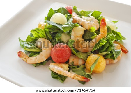 Fancy arrangement of shrimp and melon balls over lettuce. - stock photo