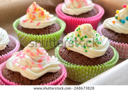 Fancy chocolate cupcakes with vanilla cream and colorful toppings and decoration - stock photo