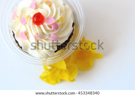 fancy cupcake decorate with yellow flower on white background. - stock photo