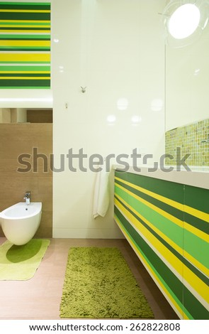 Fancy green bathroom with soft rug on marble floor - stock photo