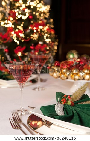 Fancy green napkins and baubles in front of a blurred christmas tree - stock photo