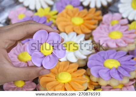 Fancy home made spring flowers sugar cookies with royal icing petals piped on. Hand Holding purple flower cookie