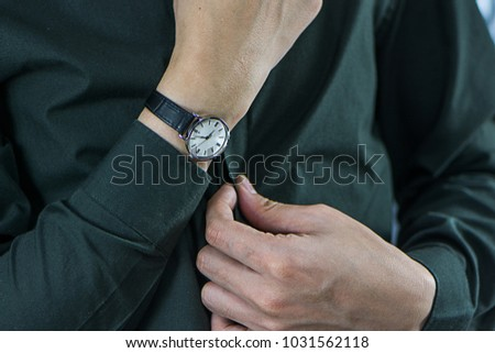 Fancy luxuryous watch for men. Businessman adjusting green shirt and watch. A hand and a watch.