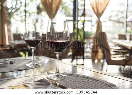 Fancy restaurant interior and served table with two glass of red wine.