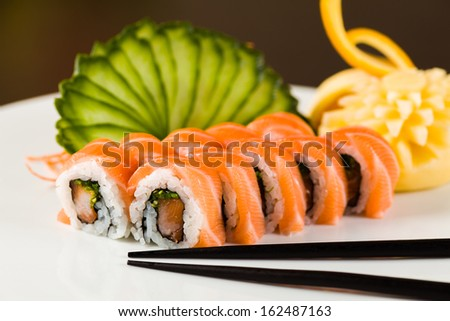 Fancy  tuna and salmon roll  on a white plate garnished with sliced cucumber and fruit carving.