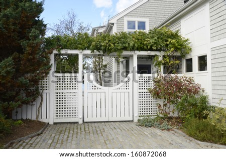 fancy white garden gate by a shingle house - stock photo