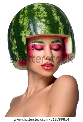 Fancy young happy girl with fresh green melon as a hard hat on an isolated white background - stock photo