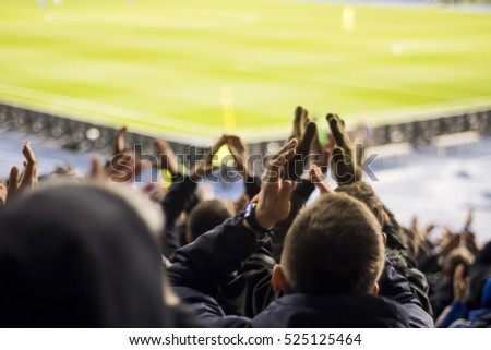 Fans at the stadium supporting their team, rear view