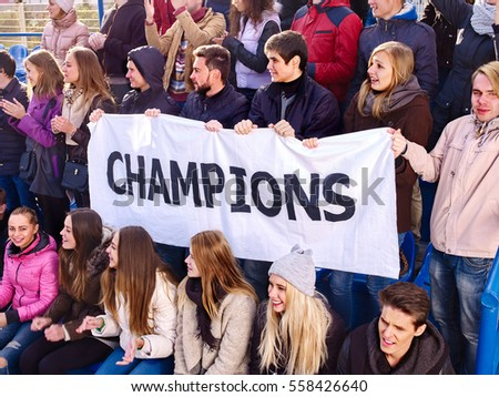 Fans cheering in stadium holding champion banner and singing on tribunes. Group young people support your favorite team.